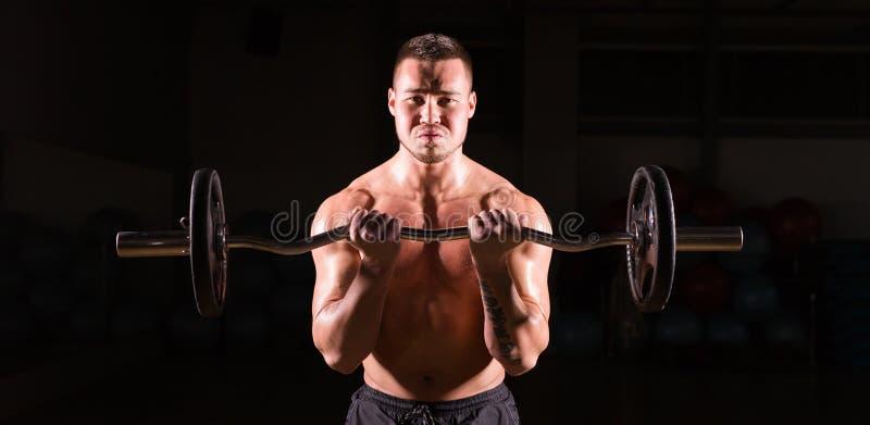 Knappe machts atletische mens met barbell De sterke bodybuilder met zes pakt, perfectioneert abs, schouders, bicepsen, triceps in royalty-vrije stock foto's