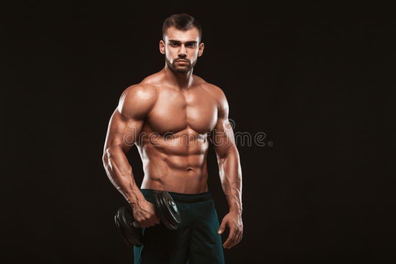 Knappe machts atletische mens in opleiding omhoog pompend spieren met domoren in een gymnastiek geïsoleerd geschiktheids spierlic royalty-vrije stock fotografie