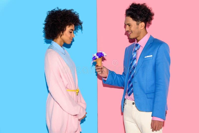 knappe man die bloemen voorstellen aan aantrekkelijke Afrikaanse vrouw op roze en blauw royalty-vrije stock fotografie