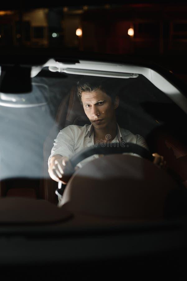 Knappe maniermens die autocabriolet drijven luxe Het leven van de nacht De verkeerslichten achter hem stock afbeelding