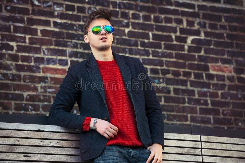Knappe maniermens toevallig jasje dragen en zonnebril die zich dichtbij bakstenen muur bevinden stock fotografie