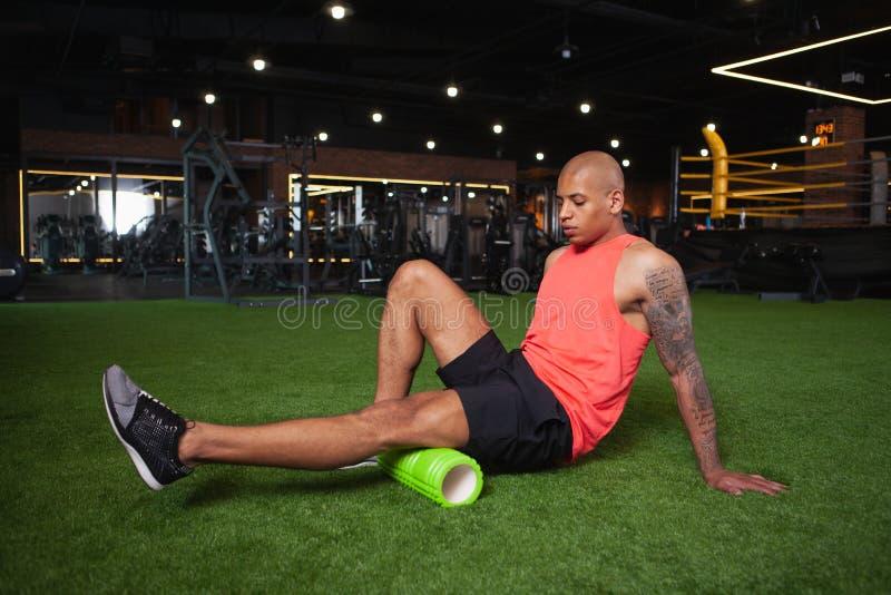 Knappe mannelijke Afrikaanse atleet die bij de gymnastiek uitwerken stock foto's
