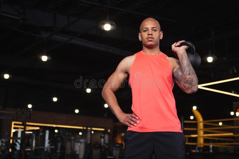 Knappe mannelijke Afrikaanse atleet die bij de gymnastiek uitwerken stock afbeelding
