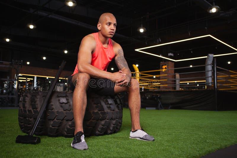 Knappe mannelijke Afrikaanse atleet die bij de gymnastiek uitwerken stock foto