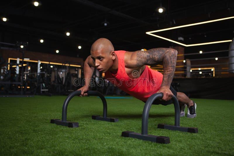 Knappe mannelijke Afrikaanse atleet die bij de gymnastiek uitwerken royalty-vrije stock afbeelding