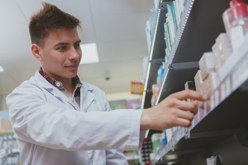 Knappe mannelijke apotheker die bij zijn drogisterij werken stock foto's
