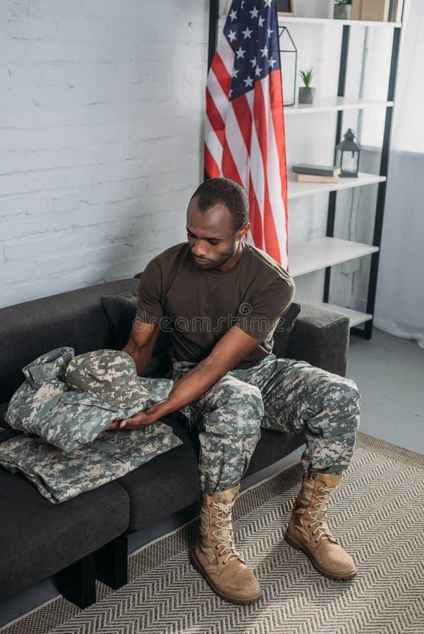 Knappe mannelijke militair die camouflagekleren vouwen stock afbeelding