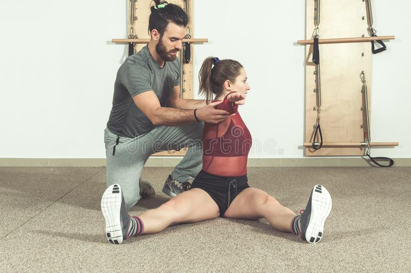 Knappe mannelijke persoonlijke trainer met een baard die jong geschiktheidsmeisje helpen om haar spieren na harde opleidingstrain stock foto's