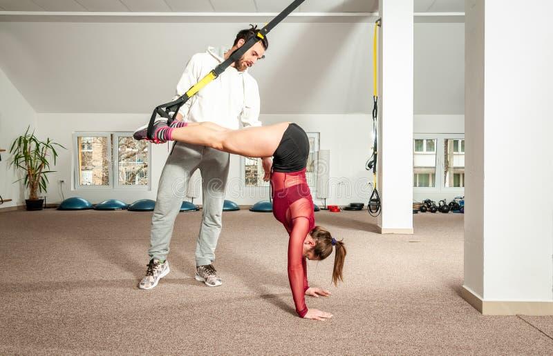 Knappe mannelijke persoonlijke trainer met een baard die jong mooi meisje voor aërobe oefening in de gymnastiek helpen, selectiev stock foto's