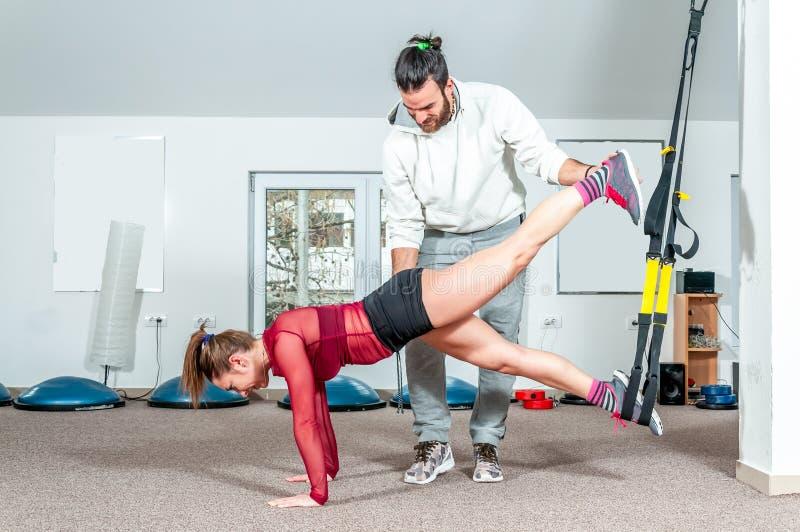 Knappe mannelijke persoonlijke trainer met een baard die jong mooi meisje voor aërobe oefening in de gymnastiek helpen, selectiev stock fotografie