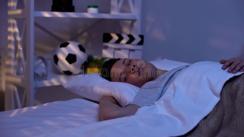 Knappe mannelijke tienerslaap vreedzaam vroeg in ochtend, veelbelovende jongen stock foto's