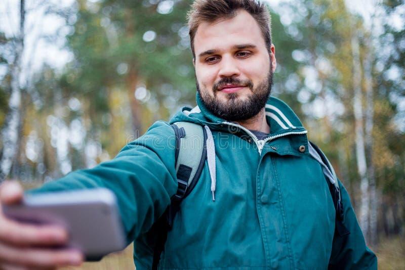 Knappe mannelijke wandelaar die een selfie in een bos nemen stock foto