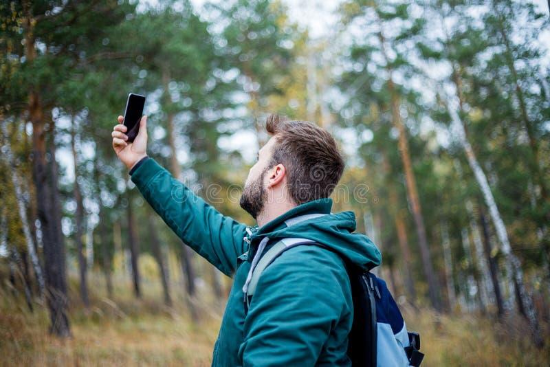 Knappe mannelijke wandelaar die een selfie in een bos nemen royalty-vrije stock afbeeldingen