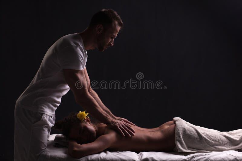 Knappe masseur die massage voor donkerbruine vrouw doen stock foto