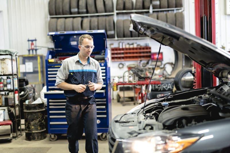 Knappe mechanische baan in het eenvormige werken aan auto royalty-vrije stock afbeeldingen