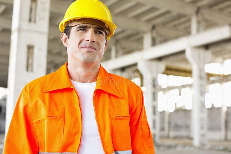 Knappe medio volwassen mens die beschermende workwear dragen bij bouwwerf stock afbeelding