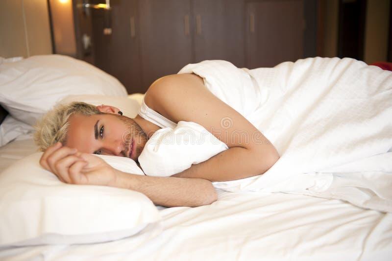 Knappe mens in bed royalty-vrije stock afbeeldingen