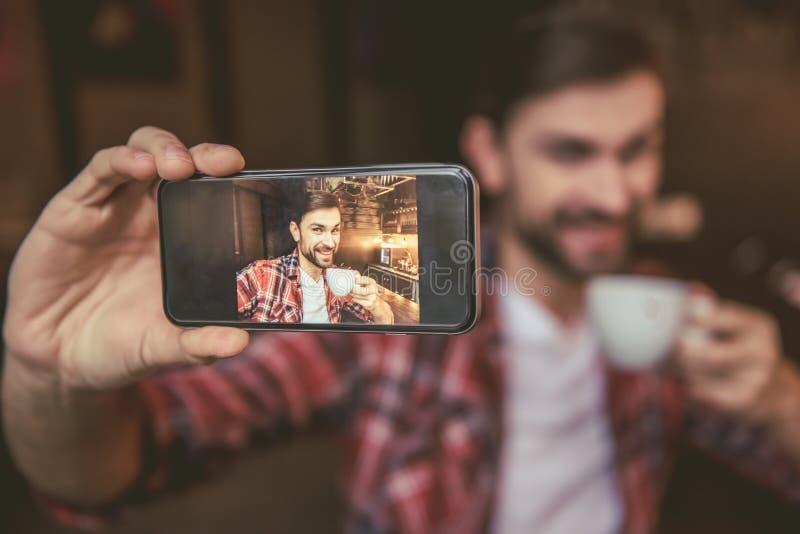 Knappe mens bij de koffie stock foto