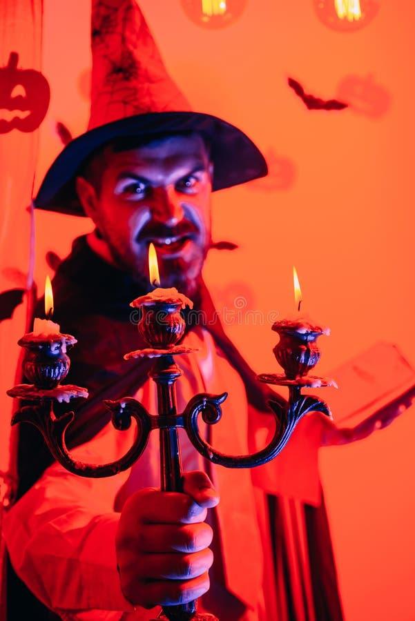 Knappe mens in de hoed van het tovenaarskostuum voor Halloween op fairytaleachtergrond Halloween, vakantieviering Grappige wijs royalty-vrije stock fotografie