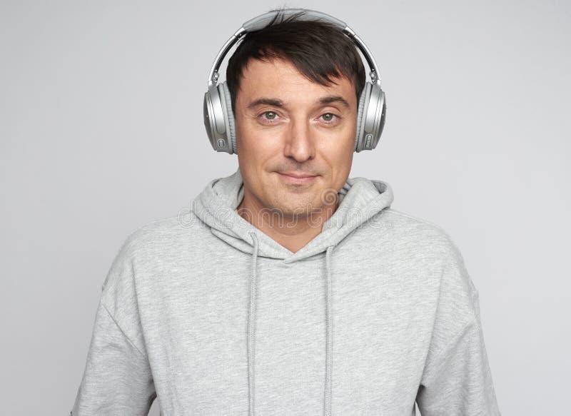Knappe mens die aan geïsoleerde muziek luisteren royalty-vrije stock foto
