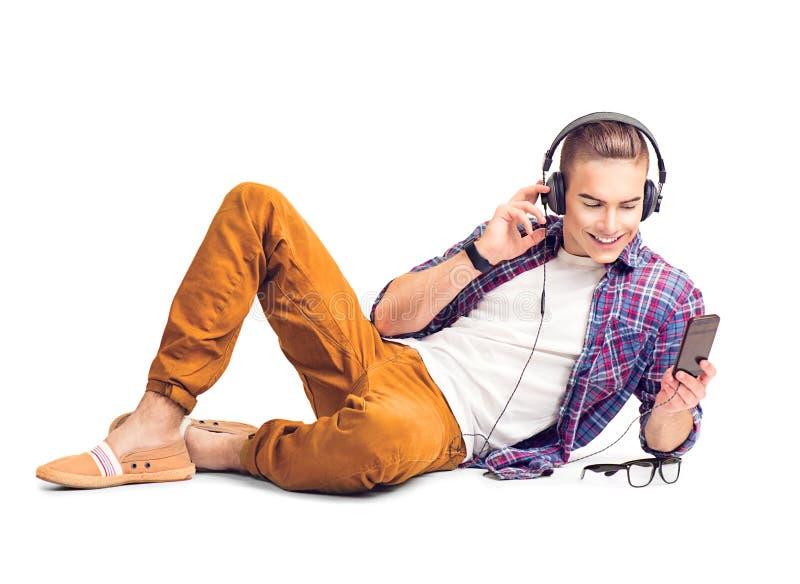 Knappe mens die aan muziek in hoofdtelefoons met smartphone luisteren stock fotografie