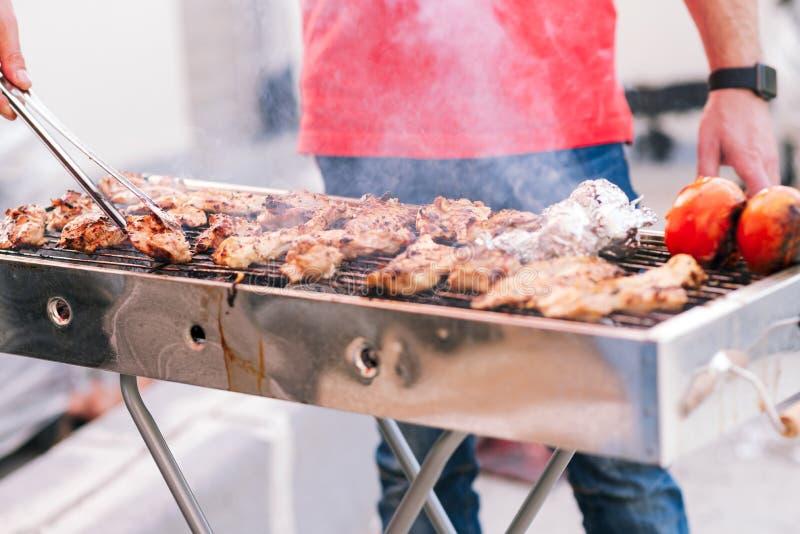 Knappe mens die barbecue voor vrienden voorbereiden Hand van de jonge mens die ??n of andere vlees en groente roosteren royalty-vrije stock afbeelding