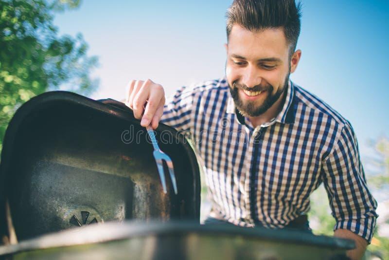Knappe mens die barbecue voor vrienden voorbereiden mensen kokend vlees op barbecue - Chef-kok die sommige worsten en pepperonis  stock afbeeldingen