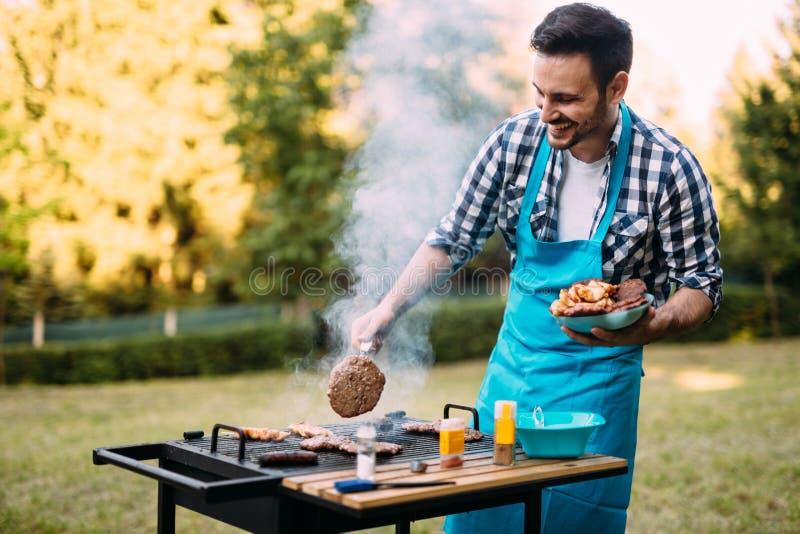 Knappe mens die barbecue voorbereiden stock afbeelding