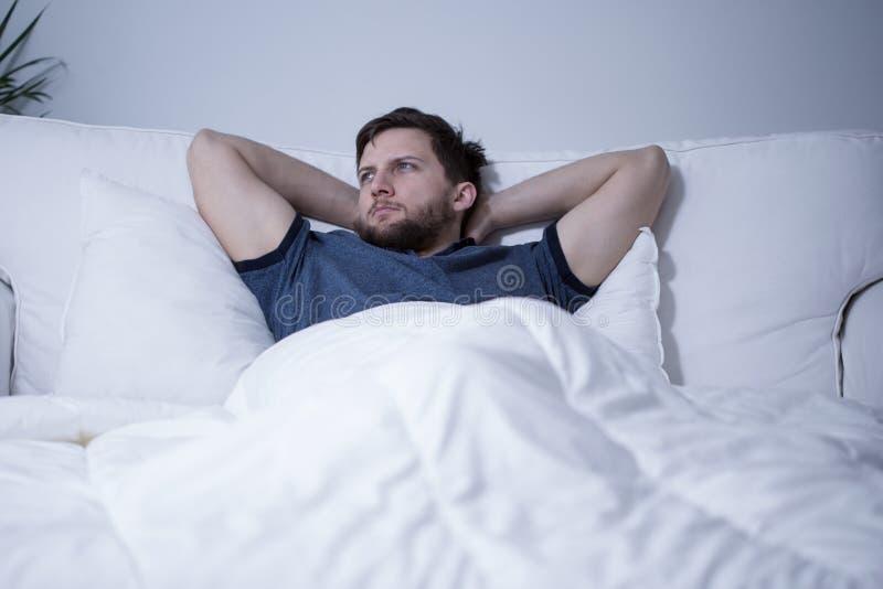 Knappe mens die in bed ligt royalty-vrije stock afbeelding
