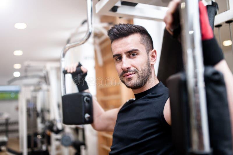 Knappe mens die bij gymnastiek, de dagelijkse routine van de borstoefening uitwerken stock afbeeldingen