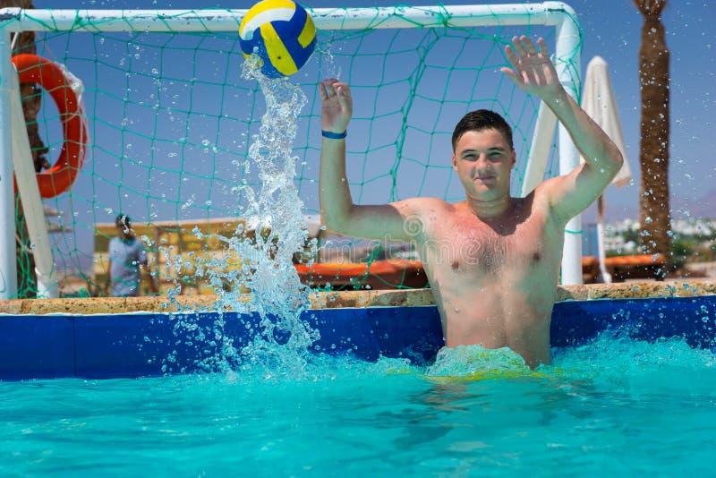 Knappe mens die de bal in polo van het pool het speelwater proberen te vangen stock afbeelding