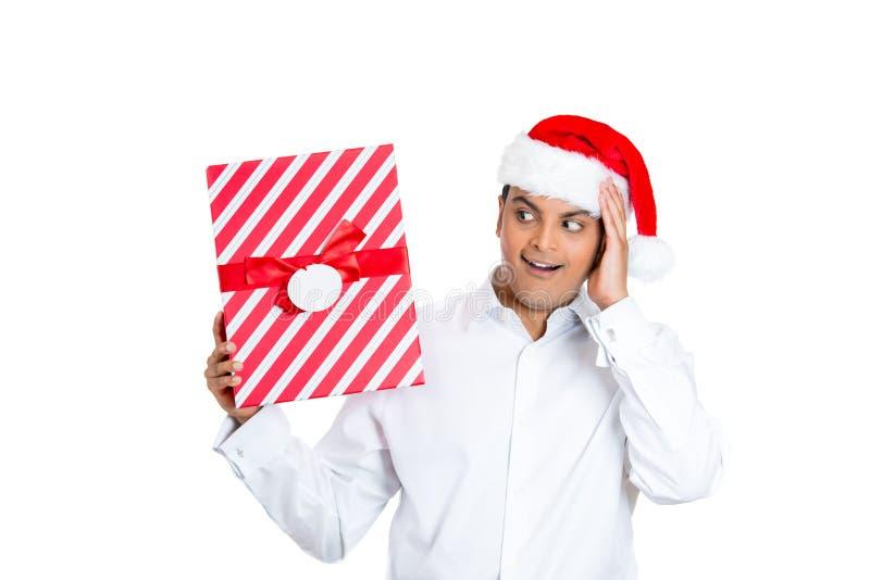 Knappe mens die in de rode hoed van de Kerstman verraste handen op wang kijkt stock afbeelding