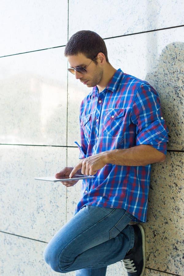 Knappe mens die digitale tablet gebruiken stock afbeelding