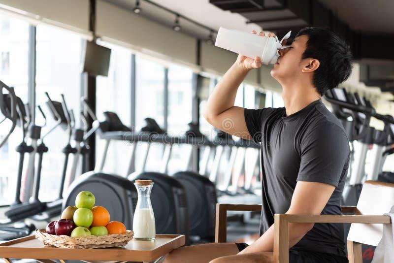 Knappe mens die eiwitschokmelk en veel soort vruchten voor dagelijks het voeden van lichaam drinken Van de mensenlevensstijlen en stock foto's
