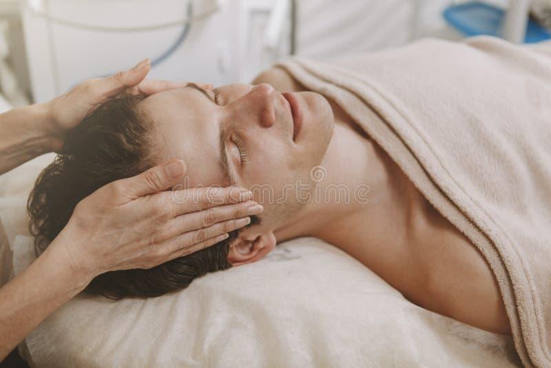 Knappe mens die gezichtsskincarebehandeling krijgen stock afbeeldingen