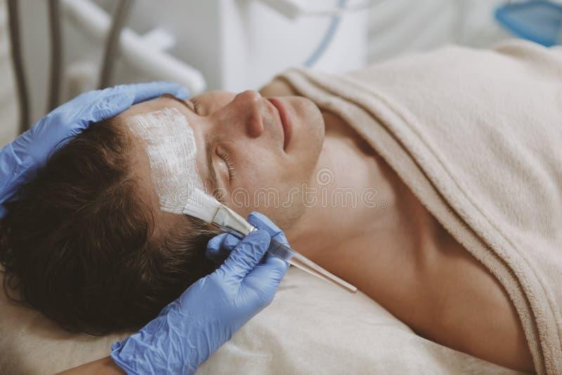 Knappe mens die gezichtsskincarebehandeling krijgen stock afbeelding