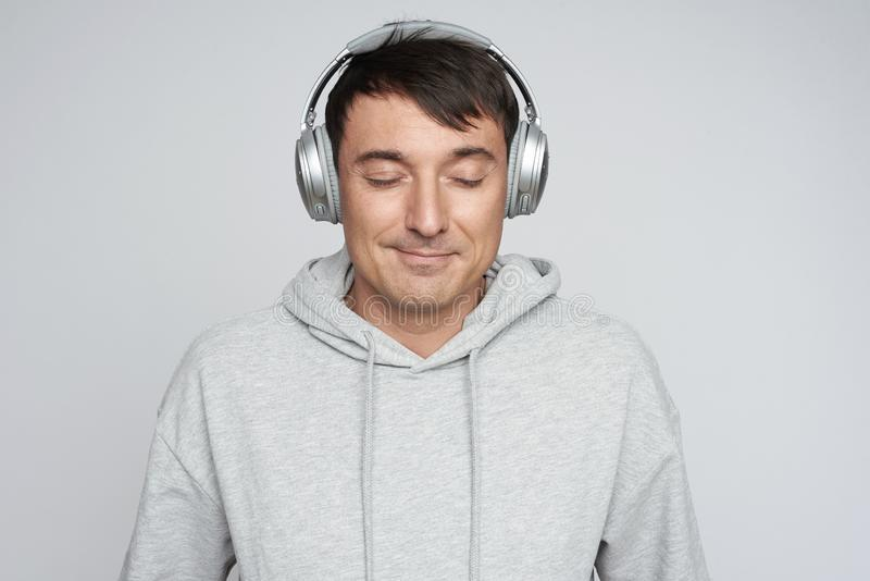 Knappe mens die in hoofdtelefoons aan muziek luisteren royalty-vrije stock afbeelding