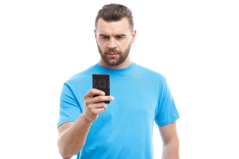 Knappe mens die met baard mobiele telefoon houden royalty-vrije stock afbeeldingen
