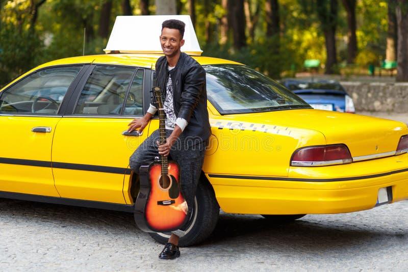 Knappe mens die met gitaar in vrijetijdskleding dichtbij gele taxi, dichtbij deur, zeker stellen zitten Horizontale mening royalty-vrije stock foto's