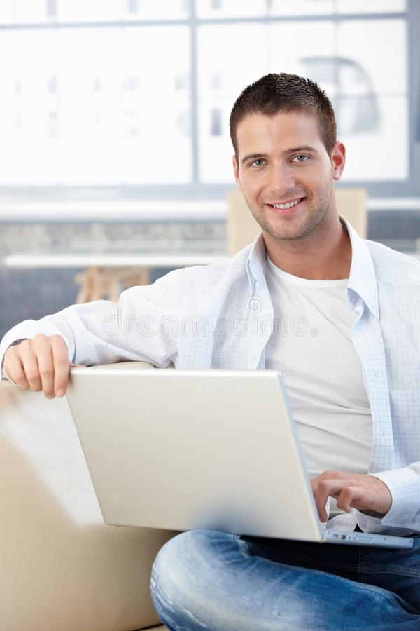 Knappe mens die met laptop op bank glimlacht royalty-vrije stock fotografie