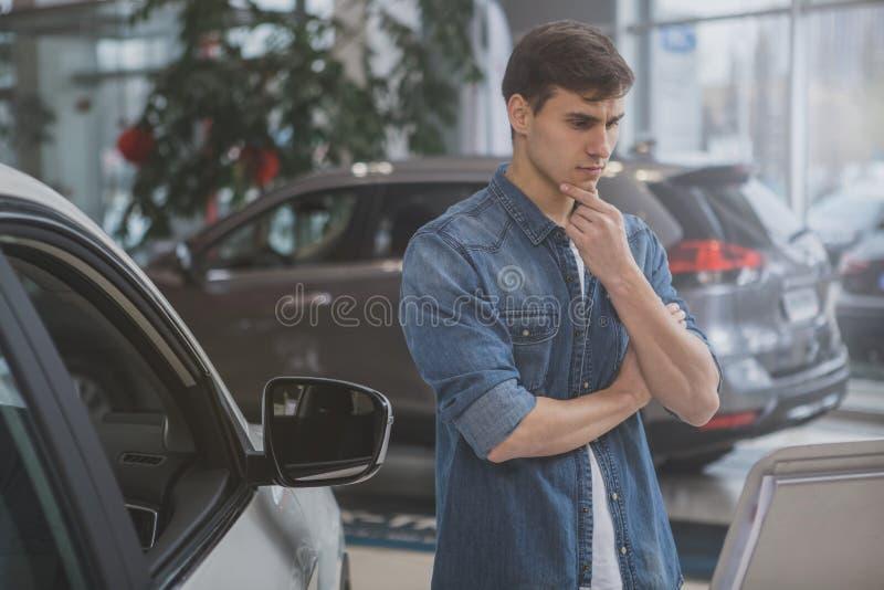 Knappe mens die nieuwe te kopen auto kiezen stock foto