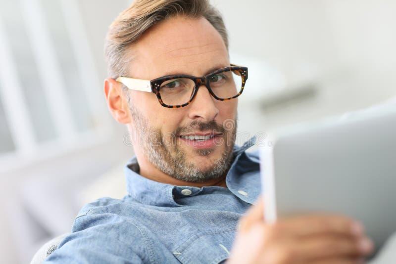 Knappe mens die oogglazen en het websurfing dragen stock fotografie