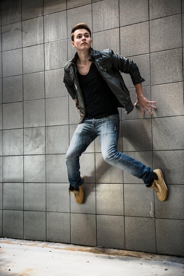Knappe mens die op de straatmuur springt royalty-vrije stock fotografie