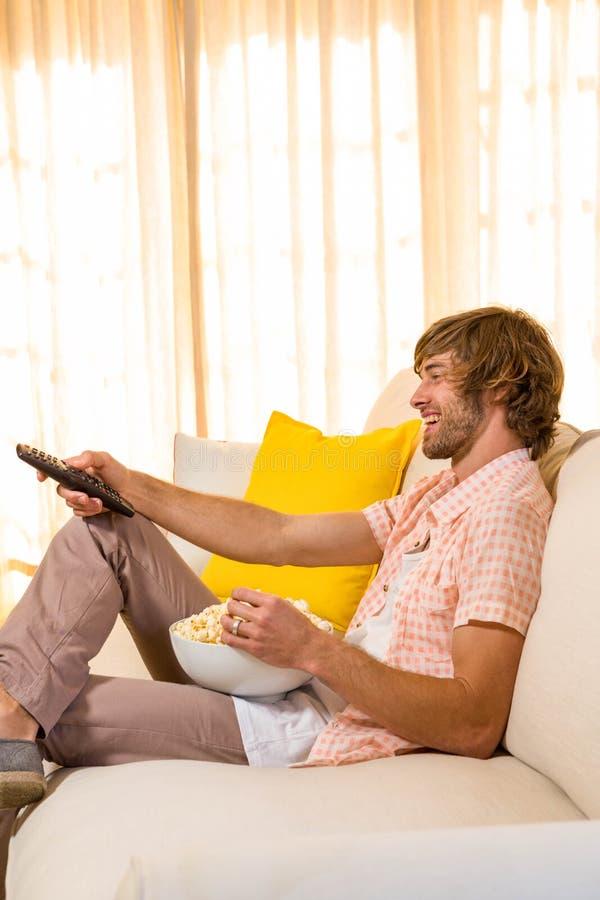 Knappe mens die op TV letten en pop graan eten stock afbeelding