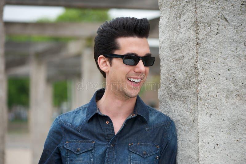 Knappe mens die in openlucht met zonnebril glimlachen royalty-vrije stock foto's