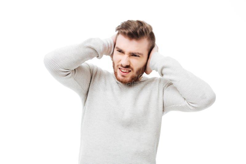 Knappe mens die oren wegens hevig lawaai over witte achtergrond behandelen De kerel kan de tribune van ` t het geïsoleerde geluid royalty-vrije stock foto's