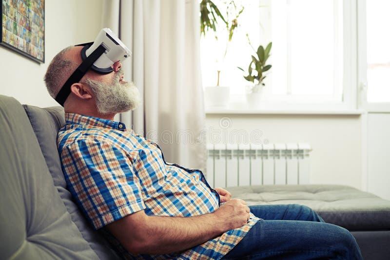 Knappe mens die pret hebben die moderne virtuele werkelijkheidshoofdtelefoon met behulp van stock foto's