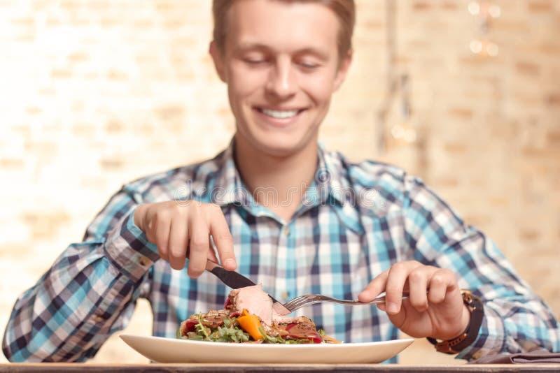 Knappe mens die salade in koffie eten royalty-vrije stock foto's