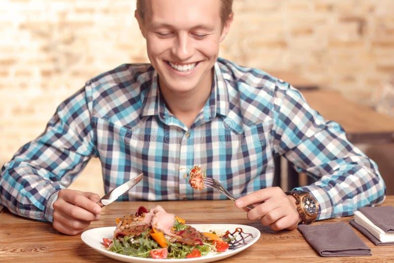 Knappe mens die salade in koffie eten stock afbeeldingen