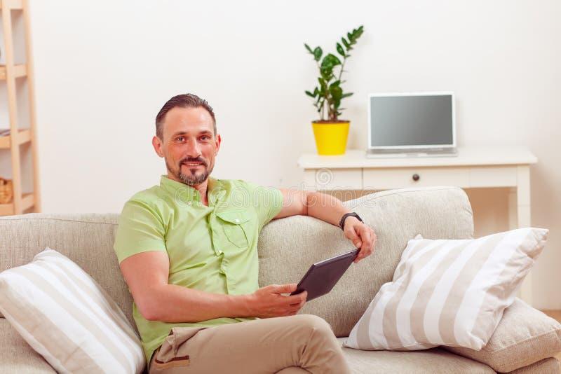 Knappe mens die tabletpc thuis met behulp van royalty-vrije stock foto's